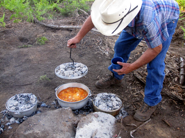 Man in cowboy hat looking into Dutch oven